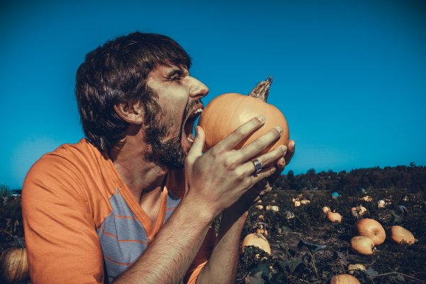 Man angrily trying to bite a pumpkin