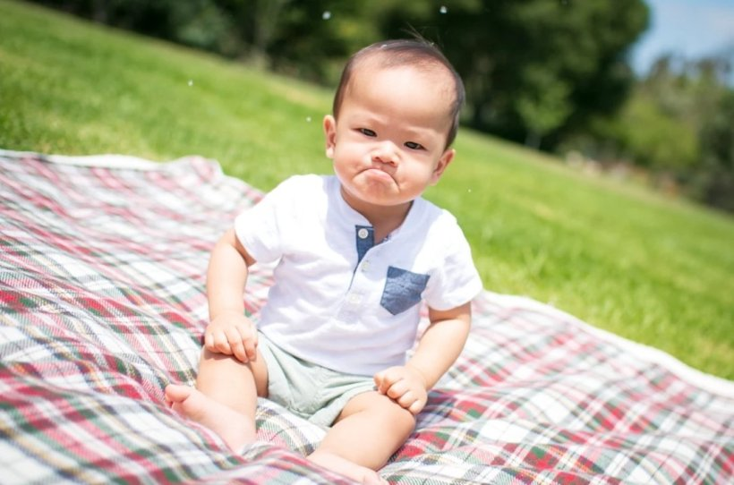 Frowning baby on plaid blanket